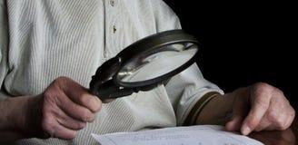 Älterer Mann, der Nachricht mit Vergrößerungsglas betrachtet stockfotos