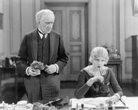 Älterer Mann, der nahe bei einer Frau an ihrem Schreibtisch steht (alle dargestellten Personen sind nicht längeres lebendes und k Lizenzfreie Stockbilder