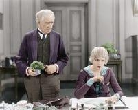 Älterer Mann, der nahe bei einer Frau an ihrem Schreibtisch steht (alle dargestellten Personen sind nicht längeres lebendes und k stockfotografie
