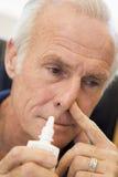 Älterer Mann, der nasalen Spray verwendet lizenzfreie stockfotos
