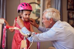 Älterer Mann, der neues Fahrrad und Sturzhelme für wenig Kind kauft stockbilder