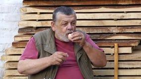 Älterer Mann, der rohes Henne ` s Ei beim Sitzen im Freien gegen Stapel von Brettern trinkt stock video footage