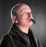 Älterer Mann, der Ruhe mit geschlossenem Mund durch Wäscheklammer hält stockfotos