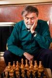Älterer Mann, der Schach spielt Stockbild