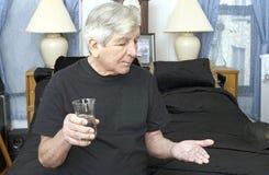 Älterer Mann, der Schlafenszeitmedizin nimmt Stockbilder