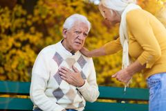 Älterer Mann, der Schmerz in der Brust erfährt, während ältere Frau ihn tröstet lizenzfreies stockbild