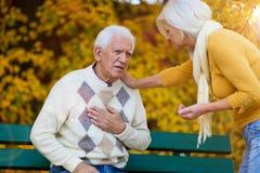 Älterer Mann, der Schmerz in der Brust erfährt, während ältere Frau ihn tröstet lizenzfreie stockfotos