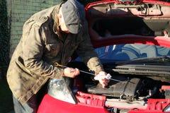 Älterer Mann, der Schmierölstand im Auto überprüft. Stockfotografie
