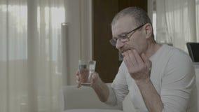Älterer Mann, der schreckliche empfindliche Zahnschmerzen hat, während er kaltes wasser- trinkt stock video footage