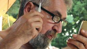 Älterer Mann, der sein Gesichtshaar 01 trimmt stock video footage