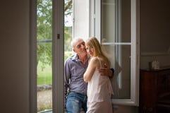 Älterer Mann, der seine junge blonde Frau nahe dem Fenster umarmt Frau, welche die Kamera betrachtet Psychologie des Beziehungs-K Lizenzfreies Stockfoto