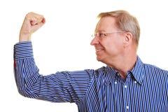 Älterer Mann, der seine Muskeln biegt Stockfotos