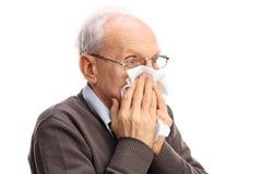 Älterer Mann, der seine Nase in einem Gewebe durchbrennt Lizenzfreie Stockfotos