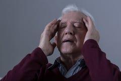 Älterer Mann, der seine Tempel berührt Lizenzfreies Stockbild