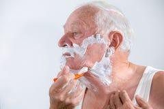 Älterer Mann, der seinen Bart rasiert Lizenzfreie Stockfotos