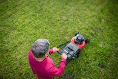 Älterer Mann, der seinen Garten - geschossen von oben mäht Stockfotografie