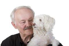 Älterer Mann, der seinen Hund anhält Stockbilder