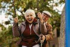 Älterer Mann, der seinen Partner auf Schwingen drückt lizenzfreie stockfotos