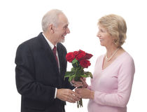 Älterer Mann, der seiner Frau Rosen gibt Stockfotos