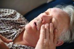 Älterer Mann, der sich mit Grippe hinlegt Stockfotografie