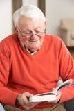 Älterer Mann, der sich zu Hause im lesenden Stuhl entspannt Stockbild