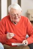Älterer Mann, der sich zu Hause im Stuhl entspannt Lizenzfreie Stockfotografie