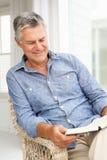 Älterer Mann, der sich zu Hause mit einem Buch entspannt Stockbild