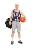 Älterer Mann in der Sportkleidung, die einen Basketball hält Lizenzfreies Stockbild