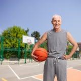 Älterer Mann in der Sportkleidung, die einen Basketball hält Lizenzfreie Stockfotografie