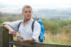 Älterer Mann, der Standort mit Handy auf Wanderung überprüft Stockbilder