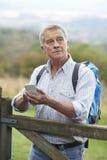Älterer Mann, der Standort mit Handy auf Wanderung überprüft Stockfoto
