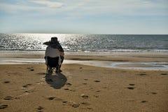 Älterer Mann, der am Strand sitzt Stockfoto