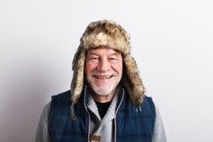 Älterer Mann in der Strickjacke, in der Westenjacke und im Pelzhut, Atelieraufnahme Stockfoto