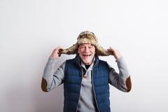 Älterer Mann in der Strickjacke, in der Westenjacke und im Pelzhut, Atelieraufnahme Stockbild