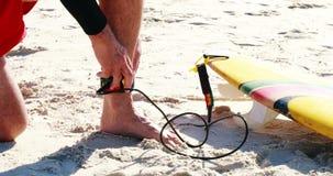 Älterer Mann, der Surfbrettleine am Knöchel bindet stock video