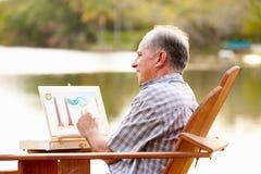 Älterer Mann, der Tabellen-Malerei-Landschaft an der im Freien sitzt stockfotos