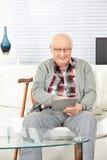 Älterer Mann, der Tablet-Computer an verwendet Stockfoto