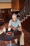 Älterer Mann, der Tablette PC im Hotel verwendet Stockbilder