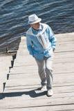 Älterer Mann, der tagsüber durch Pflasterung auf dem Flussufer geht Lizenzfreies Stockfoto