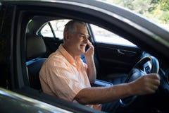 Älterer Mann, der am Telefon im Auto spricht Lizenzfreies Stockbild
