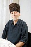 Älterer Mann, der am Tisch sitzt stockbild