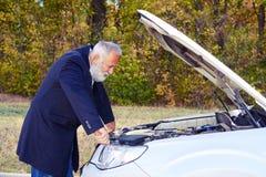 Älterer Mann, der unter der Haube des Zusammenbruchautos schaut Stockfotos