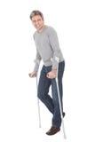 Älterer Mann, der unter Verwendung der Krückeen geht Stockfotos