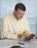 Älterer Mann, der USA-Steuerformular 1040 für 2012 vorbereitet Lizenzfreies Stockbild
