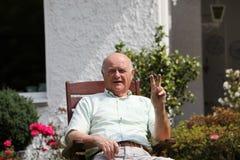 Älterer Mann, der V-Zeichen gibt stockfoto