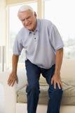 Älterer Mann, der versucht, sich hinzusitzen Stockbilder