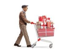Älterer Mann, der voll einen Einkaufswagen von eingewickelten Geschenken drückt lizenzfreie stockfotografie