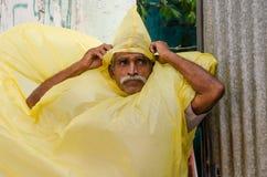 Älterer Mann, der vom Regen unter Verwendung der Regenjacke sich versteckt Stockbild