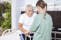 Älterer Mann, der von der weiblichen Krankenschwester In Using Walker unterstützt wird stockbild