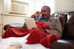 Älterer Mann, der warme Unterdecke mit Fotografie hält Stockbilder